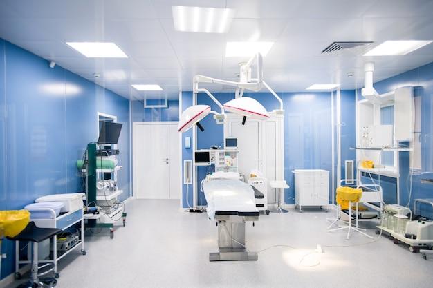 Wnętrze sali operacyjnej w nowoczesnych klinikach ze wszystkimi niezbędnymi urządzeniami wzdłuż ścian i stołem operacyjnym pośrodku z lampami powyżej
