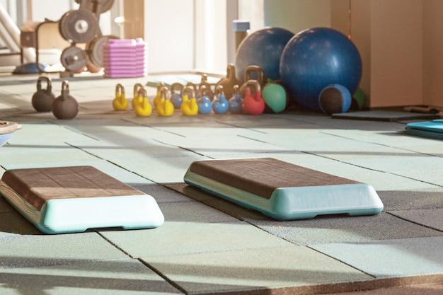 Wnętrze sali rehabilitacyjnej ze sprzętem: piłki, maty, stopnie