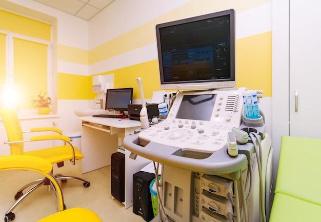 Wnętrze sali szpitalnej z aparatem usg i łóżkiem