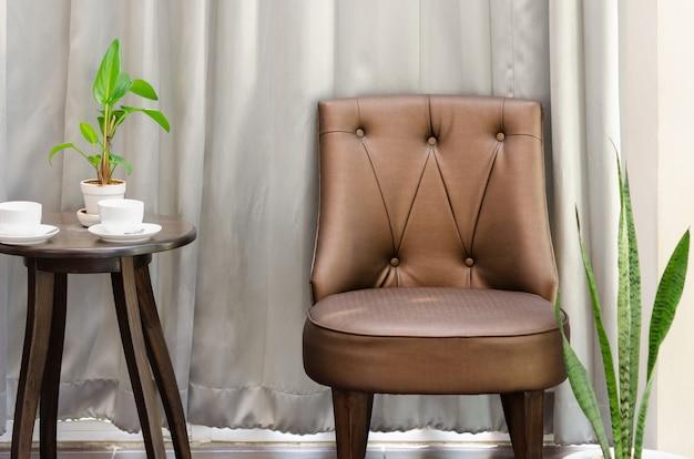 Wnętrze salonu lub holu z brązowym krzesłem i okrągłym stolikiem z filiżanką kawy i zieloną rośliną