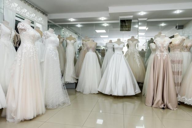 Wnętrze salonu ślubnego, suknie ślubne na manekinach