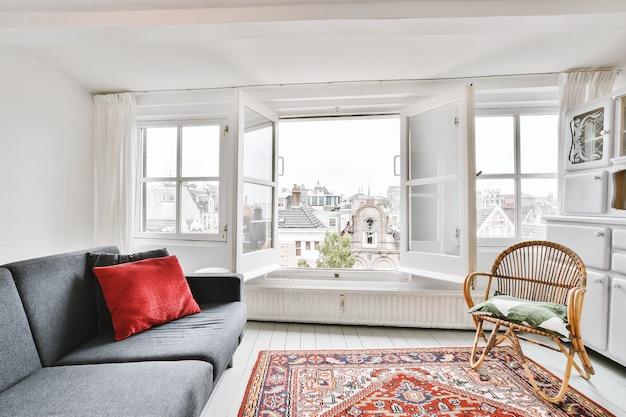 Wnętrze salonu z białą ścianą z sofą i rattanowym krzesłem na perskim dywanie z oknami z widokiem na stare miasto