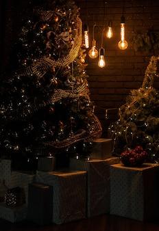 Wnętrze salonu z jasnymi lampami vintage z choinką i pudełkami na prezenty wieczorem. czekam na nowy rok.
