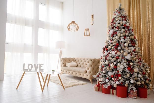 Wnętrze salonu z sofą, stołem, lampą podłogową i oknem panoramicznym. drzewko świąteczne