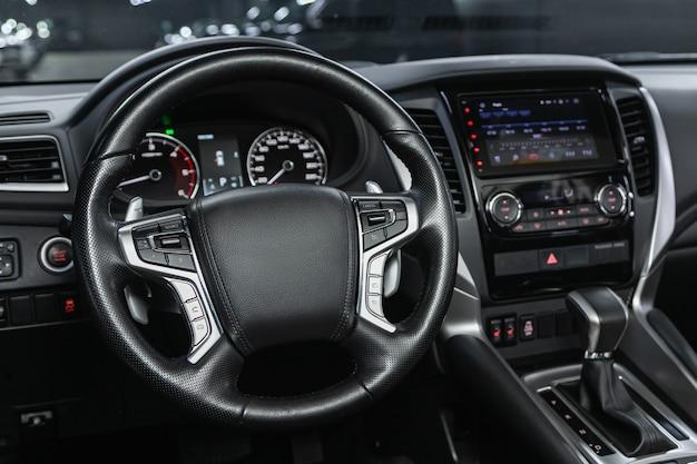 Wnętrze samochodu - kierownica, dźwignia zmiany biegów i deska rozdzielcza, klimatyzacja, prędkościomierz, wyświetlacz.