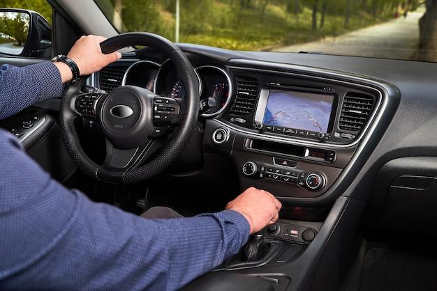 Wnętrze samochodu klasy premium z dynamicznymi liniami zwrotnymi kamery cofania i asystentem parkowania. system wspomagania kierowcy podczas parkowania. pomóż w wyborze opcji w luksusowym samochodzie