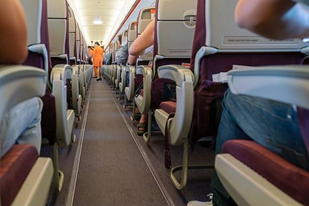 Wnętrze samolotu z pasażerami na siedzeniach i stewardesa w pomarańczowym mundurze przy nawie
