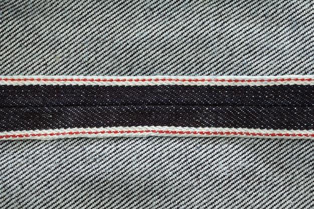 Wnętrze surowego denimu ciemne spranie indygo niebieskie dżinsy tekstura tło pokazują czerwoną linię brzegów