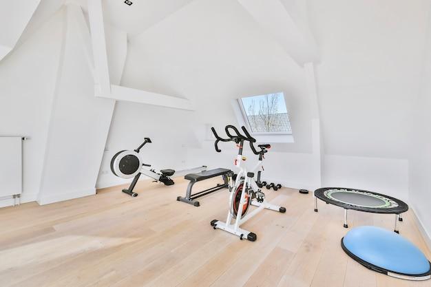 Wnętrze świetlicy wyposażone w sprzęt do ćwiczeń ławeczkę i maszynę rowerową