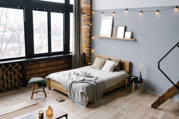 Wnętrze sypialni w nowoczesnym stylu skandynawskim z szarymi drewniano-ceglanymi ścianami, wygodnym podwójnym łóżkiem, panoramicznym oknem
