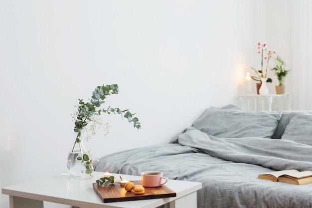 Wnętrze sypialni z bukietem, świecami i filiżanką herbaty