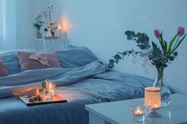 Wnętrze sypialni z kwiatami, świecami i filiżanką herbaty