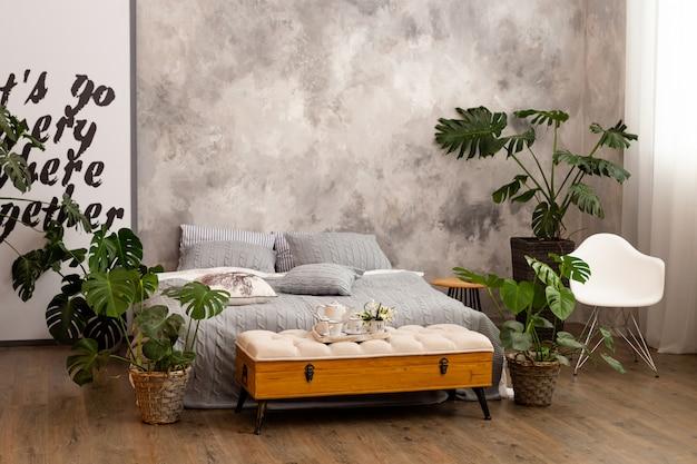 Wnętrze sypialni z zielonymi roślinami, poduszkami.