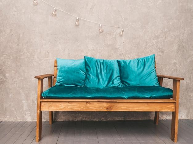 Wnętrze szarej ściany ze stylową tapicerowaną niebieską i drewnianą nowoczesną sofą, wiszące lampy