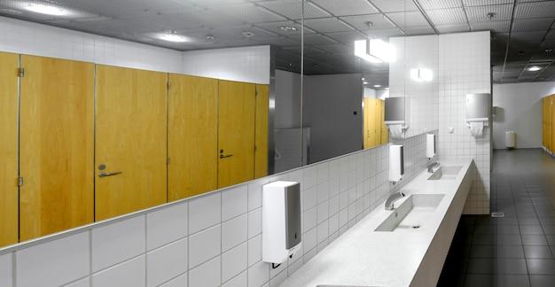 Wnętrze toalety publicznej z bateriami umywalkowymi i kabinami wc