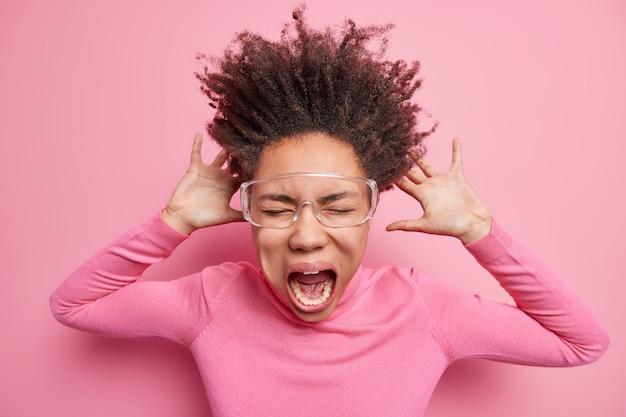 Wnętrze ujęcia emocjonalnej afroamerykanki, która ma zamknięte oczy, krzyczy bardzo głośno, będąc super szaloną