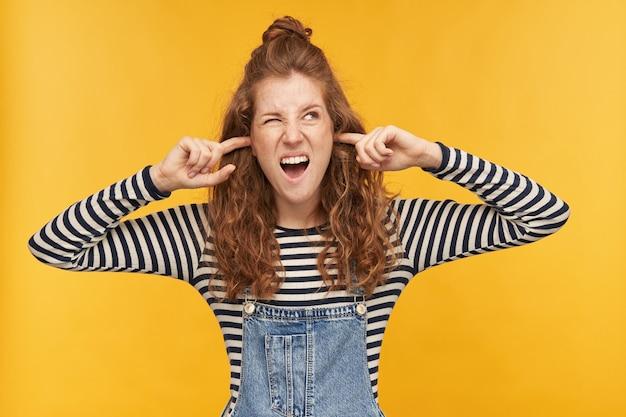 Wnętrze ujęcia młodej niezadowolonej rudej kobiety, odwraca wzrok z negatywnym wyrazem twarzy, zatyka palcami uszy i wścieka się na hałaśliwych sąsiadów. na białym tle nad żółtą ścianą