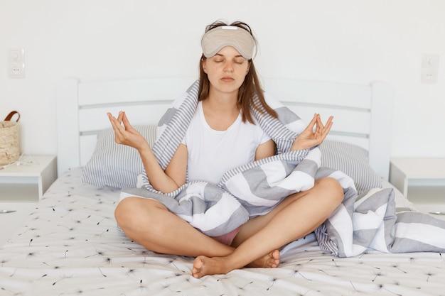 Wnętrze ujęcia zrelaksowanej kobiety w masce do spania i owiniętej w koc, siedzącej w pozycji jogi na łóżku w jasnej sypialni z zamkniętymi oczami, próbującej się uspokoić, medytującej rano.