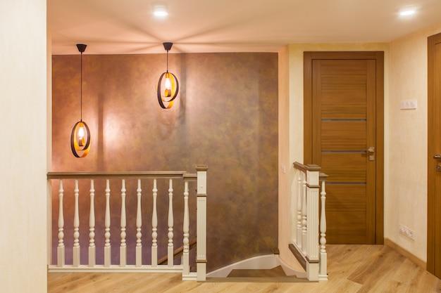 Wnętrze w stylu klasycznym w dwupoziomowym mieszkaniu. białe drewniane schody w holu na drugim piętrze z nowoczesnym oświetleniem.