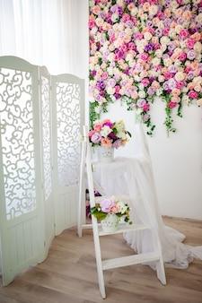 Wnętrze w stylu prowansalskim z białym ekranem, jasną ścianą kwiatową, wiaderkiem ze sztucznymi kwiatami