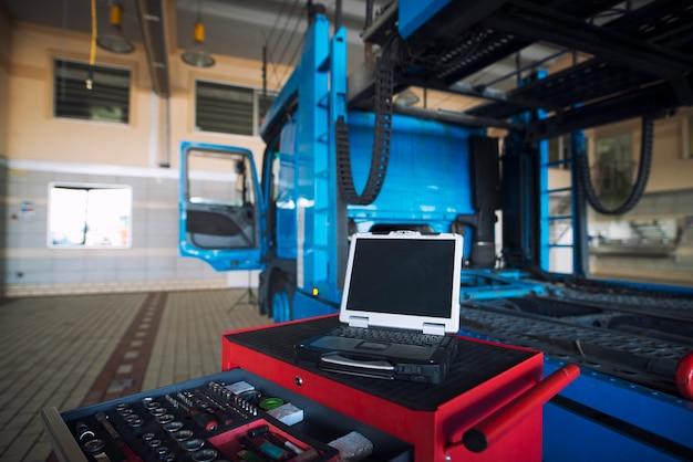 Wnętrze warsztatu samochodowego z wózkiem narzędziowym i narzędziem diagnostycznym laptopa do obsługi pojazdów ciężarowych