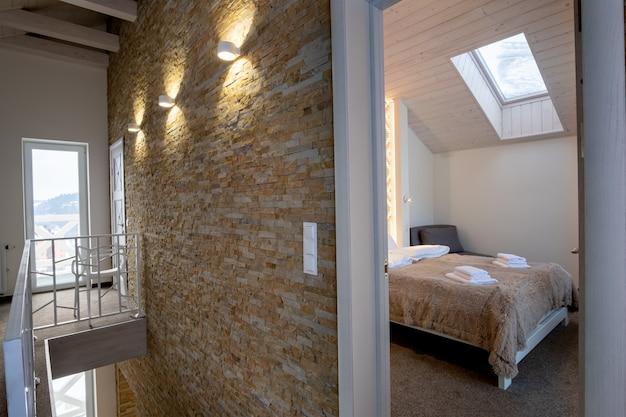 Wnętrze współczesnego domu z przestronnym przedpokojem, drzwiami do sypialni i balustradą schodów w nowoczesnym stylu.