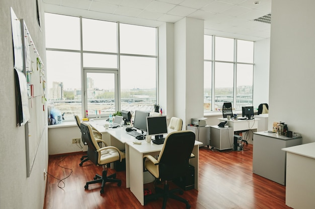 Wnętrze współczesnego dużego biura w nowoczesnym centrum z biurkami, monitorami komputerowymi, białymi skórzanymi fotelami i innymi rzeczami