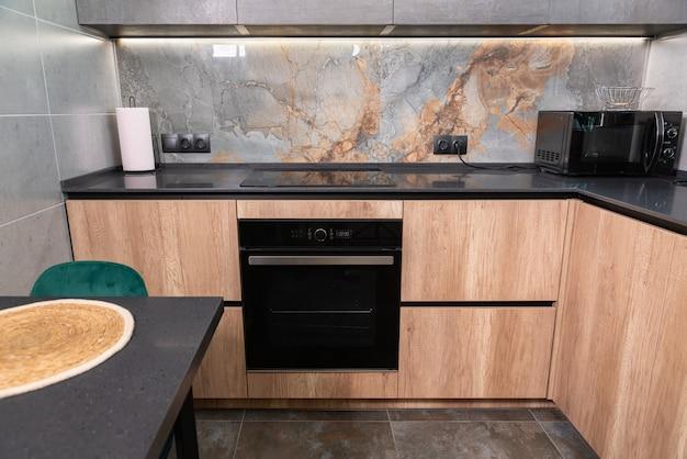 Wnętrze wyposażonej kuchni z drewnianymi szafkami i wbudowanymi urządzeniami z szarymi kamiennymi blatami i marmurowym tyłem, oglądane za dopasowanym stołem