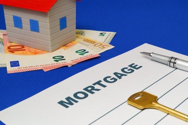 Wniosek o kredyt hipoteczny, długopis, dom, pieniądze i klucz na niebieskim stole.
