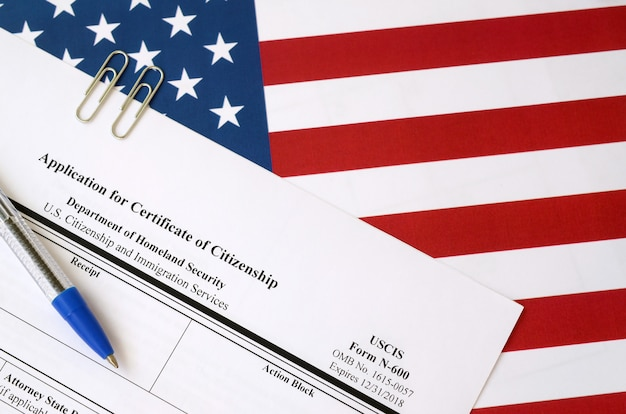 Wniosek o wydanie n-600 na pusty formularz zaświadczenia o obywatelstwie znajduje się na fladze stanów zjednoczonych z niebieskim długopisem z departamentu bezpieczeństwa wewnętrznego