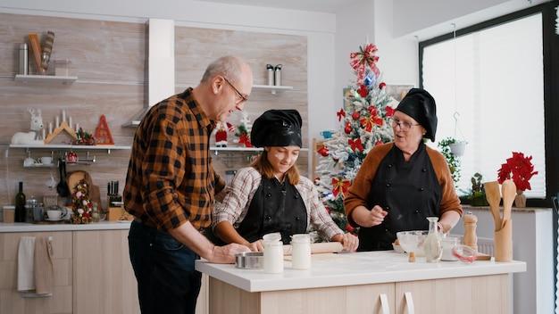 Wnuczek ubrany w fartuch kuchenny przygotowujący domowe ciasto na pyszne ciasteczka