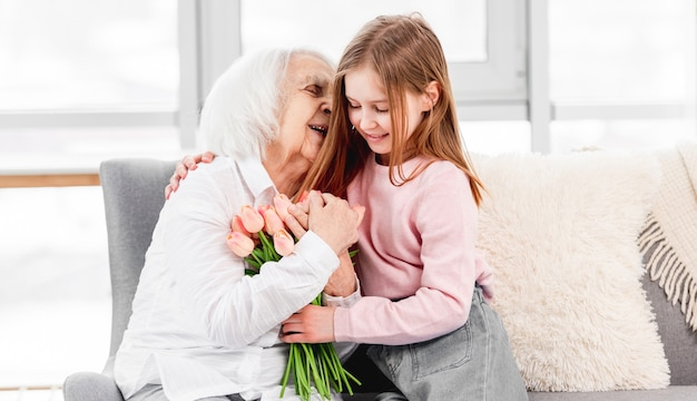 Wnuczka daje babci bukiet kwiatów tulipanów i przytula ją w domu