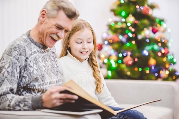 Wnuczka i dziadek czytali książkę przy choince
