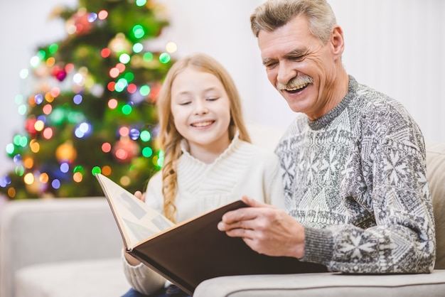 Wnuczka i dziadek oglądają album ze zdjęciami przy choince