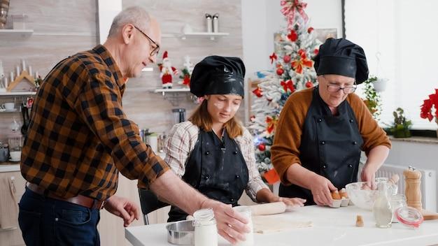 Wnuczka przygotowująca deser piernikowy robi tradycyjne domowe ciasto