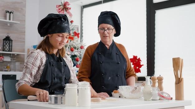 Wnuczka przygotowuje domowe ciasto na pierniki za pomocą wałka do pieczenia