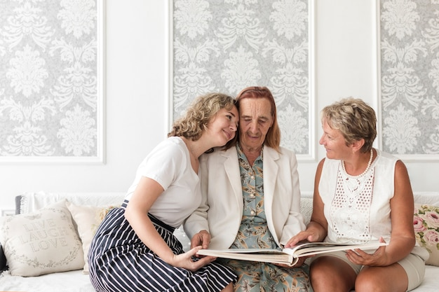 Wnuczka przytulanie babci patrząc album fotograficzny w domu