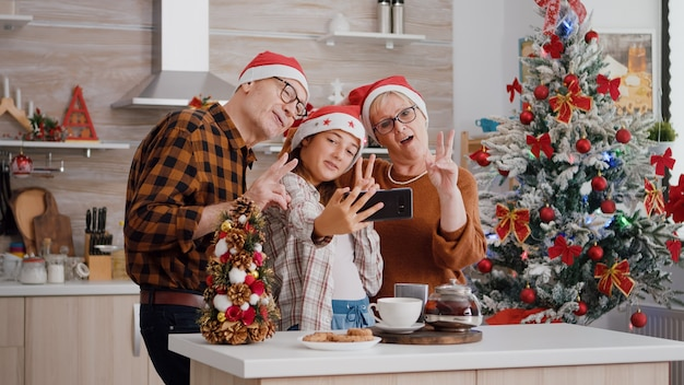 Wnuczka robi selfie za pomocą smartfona z dziadkami podczas obchodów świąt bożego narodzenia
