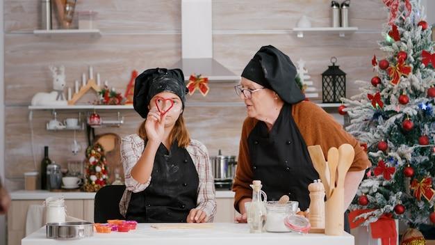 Wnuczka w fartuchu kulinarnym wybierająca kształt ciastek robiących tradycyjne domowe ciasto piernikowe...