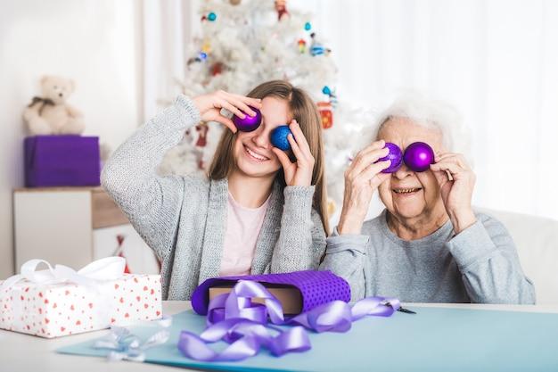 Wnuczka w santa hat gra ozdobne kulki na boże narodzenie