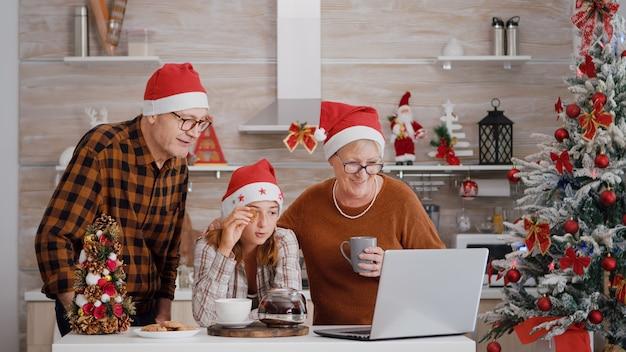 Wnuczka z dziadkami rozmawia ze zdalnymi rodzicami podczas wideokonferencji online na la...