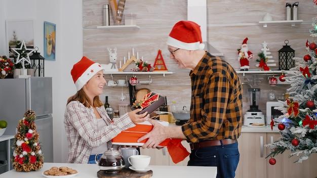 Wnuczka z dziadkiem dzielą się prezentem świątecznym ze wstążką