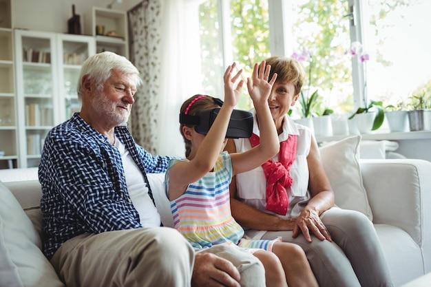 Wnuczka za pomocą zestawu słuchawkowego wirtualnej rzeczywistości z dziadkami w salonie