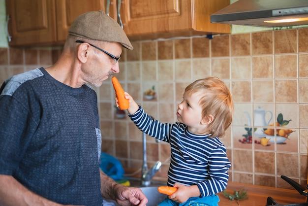 Wnuk daje dziadkowi marchewkę