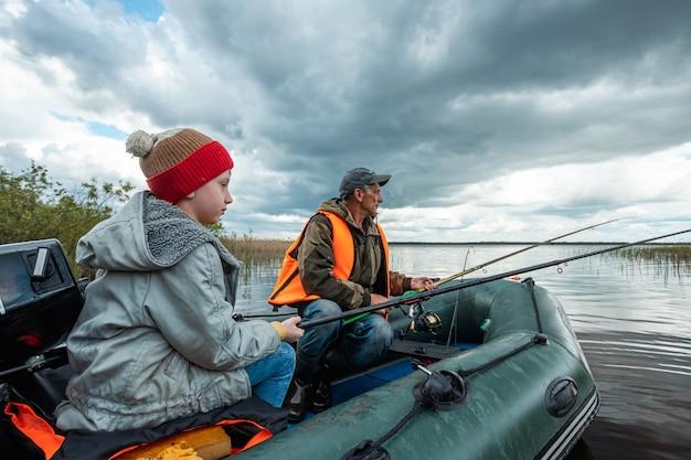 Wnuk i dziadek razem łowią ryby z łodzi na jeziorze.