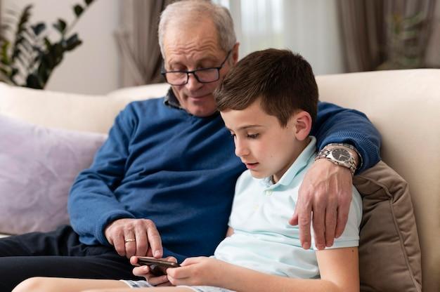 Wnuk i dziadek relaksujący na kanapie
