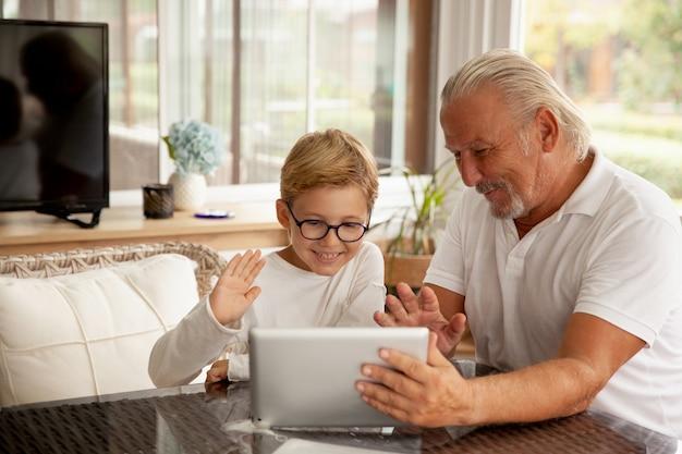 Wnuk i dziadek rozmawiają przez aplikację do czatu wideo na tablecie