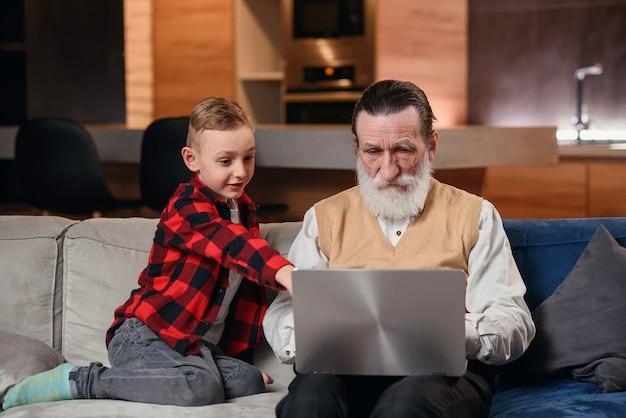 Wnuk uczy swojego dziadka obsługi komputera.
