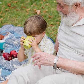 Wnuk wysoki kąt pije herbatę