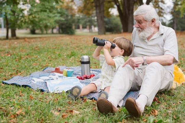 Wnuk z dziadkiem patrząc przez lornetkę